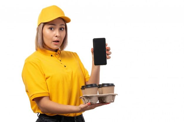 Молодая женщина-курьер в желтой рубашке, желтой кепке и черных джинсах, держащая кофе и смартфон, вид спереди