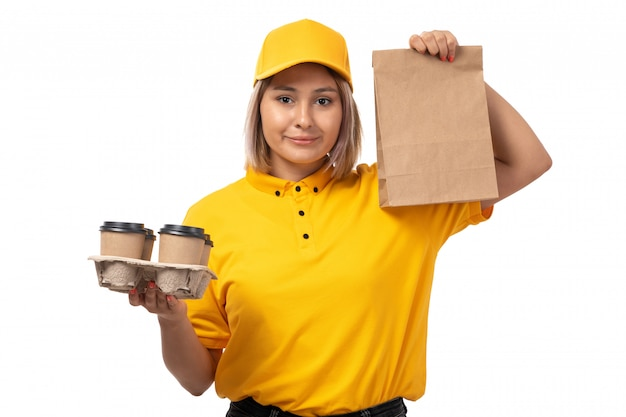 Молодая женщина-курьер в желтой рубашке, желтой кепке и черных джинсах, улыбаясь, держит пакет с едой и кофейные чашки, вид спереди