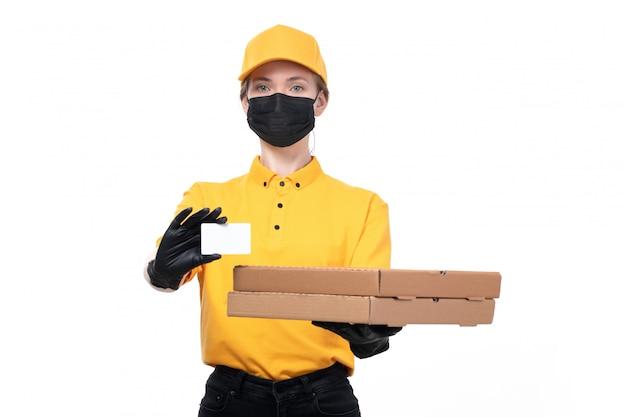 Вид спереди молодая женщина-курьер в желтой форме, черные перчатки и черная маска, белая карточка и коробки с едой