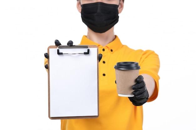 Молодая женщина-курьер в желтой униформе, черные перчатки и черная маска, держащая чашку кофе и блокнот, вид спереди