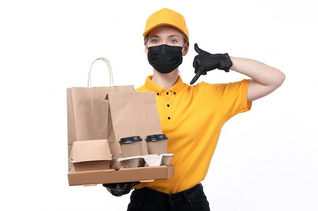Вид спереди молодая женщина-курьер в желтой форме, черные перчатки и черная маска, держащая кофейные чашки и доставку пакетов с едой
