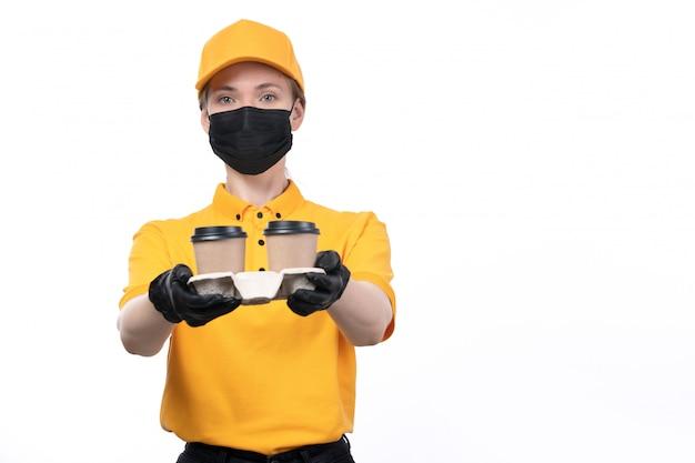 Вид спереди молодая женщина-курьер в желтой форме, черные перчатки и черная маска, держащая кофейные чашки, доставляющая заказ