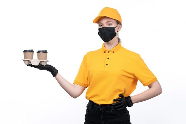 Молодая женщина-курьер в желтой униформе, черные перчатки и черная маска, держащая доставку кофейных чашек, вид спереди