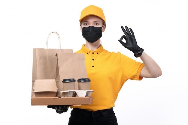 Вид спереди молодая женщина-курьер в желтой униформе, черные перчатки и черная маска, держащая пакеты для доставки еды из кофейных чашек