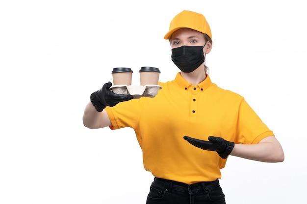 Молодая женщина-курьер в желтой униформе, черные перчатки и черная маска, держащая кофейные чашки, вид спереди