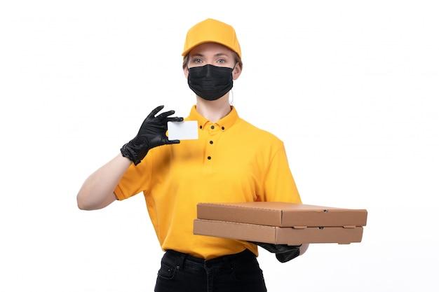 Молодая женщина-курьер в желтой униформе, черные перчатки и черная маска, держащая пакеты для доставки еды и белую карточку, вид спереди