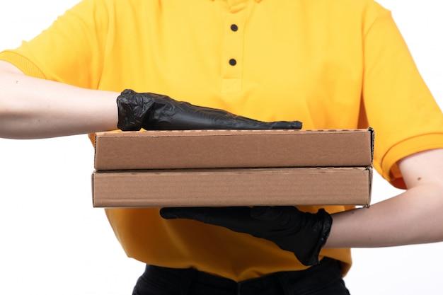 Молодая женщина-курьер в желтой униформе, черные перчатки и черная маска, держащая посылки с доставкой еды, вид спереди