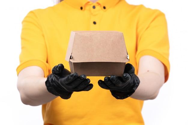 Молодая женщина-курьер в желтой форме, черные перчатки и черная маска, держащая пакет с едой, вид спереди