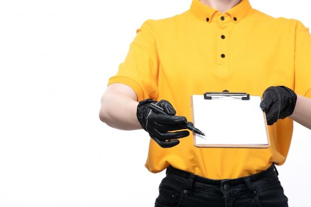 Молодая женщина-курьер в желтой униформе, черных перчатках и черной маске держит блокнот и просит подписи.