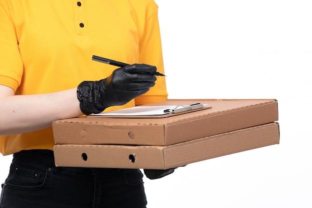 Молодая женщина-курьер в желтой униформе, черные перчатки и черная маска, держащая коробки с пиццей и приказывающая писать, вид спереди