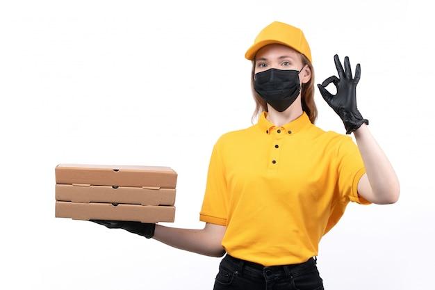 黄色の均一な黒い手袋とピザの箱を保持している黒いマスクの正面の若い女性の宅配便