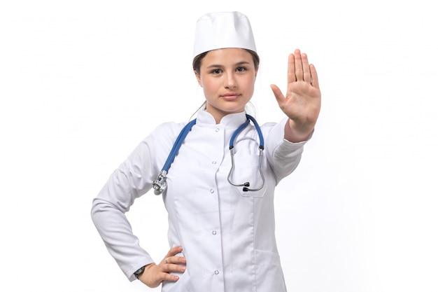 Вид спереди молодая женщина-врач в белом медицинском костюме и белой кепке с синим стетоскопом, показывая знак остановки