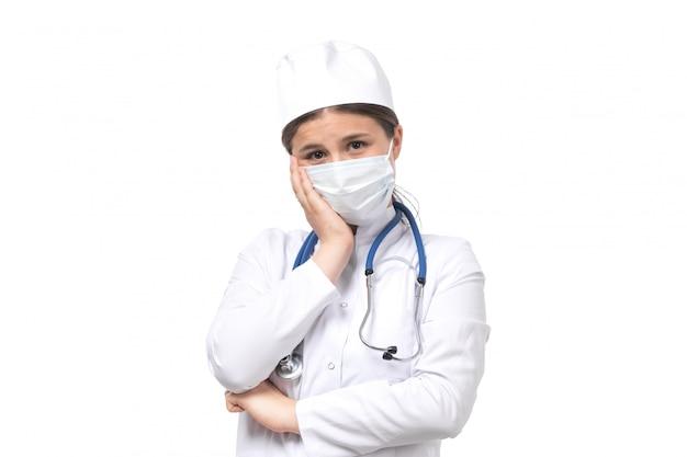 白いマスクを身に着けている青い聴診器で白い医療訴訟で正面若い女医
