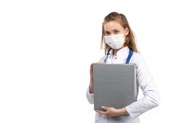 Вид спереди молодая женщина-врач в белом медицинском костюме со стетоскопом в белой защитной маске держит серые файлы на белом
