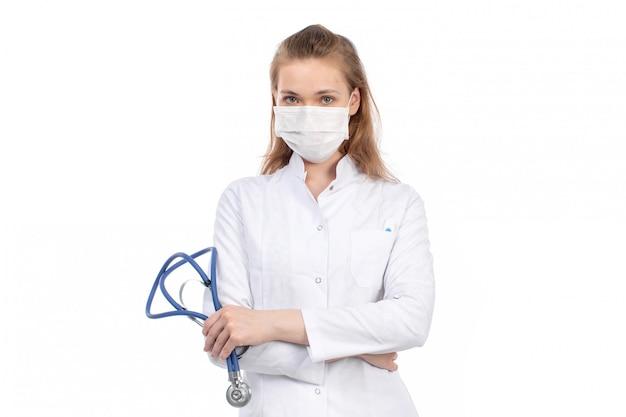 Вид спереди молодая женщина-врач в белом медицинском костюме со стетоскопом в белой защитной маске на белом