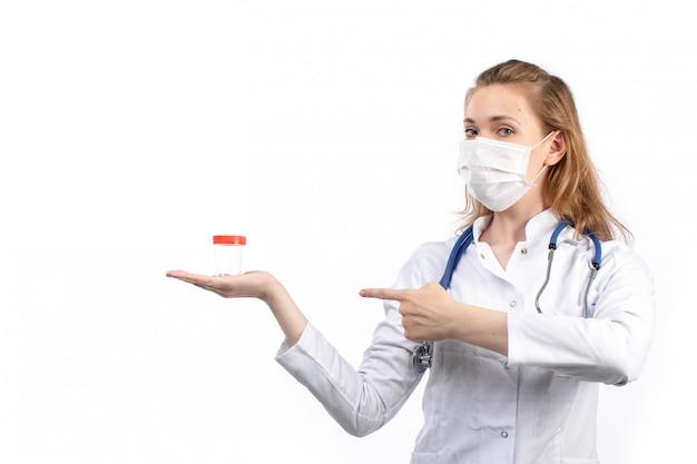 Вид спереди молодая женщина-врач в белом медицинском костюме со стетоскопом в белой защитной маске позирует держа колбу на белом