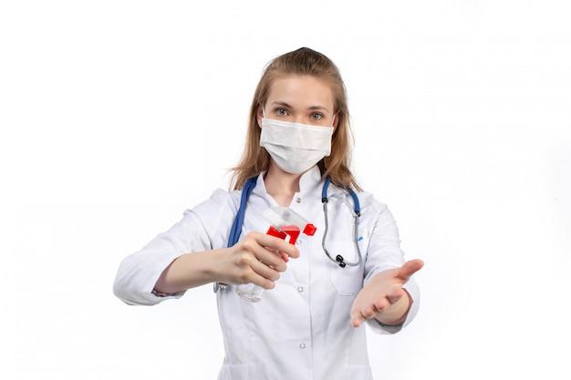 Вид спереди молодая женщина-врач в белом медицинском костюме со стетоскопом в белой защитной маске позирует держа спрей на белом