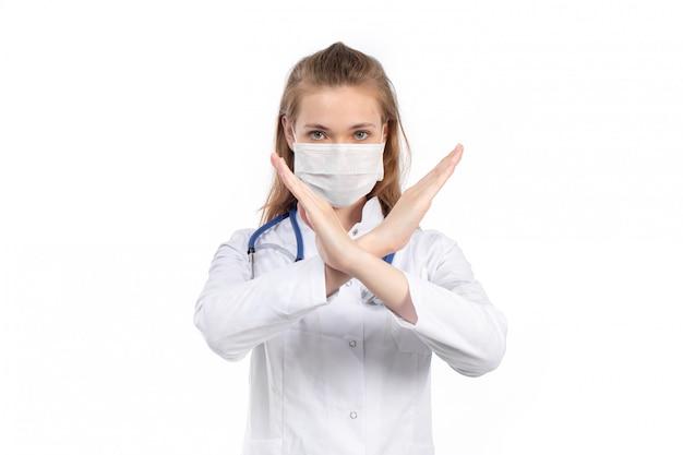 Вид спереди молодая женщина-врач в белом медицинском костюме со стетоскопом в белой защитной маске позирует, показывая знак запрета на белом