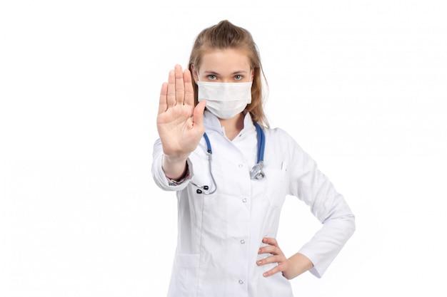 Вид спереди молодая женщина-врач в белом медицинском костюме со стетоскопом в белой защитной маске позирует, показывая знак остановки на белом