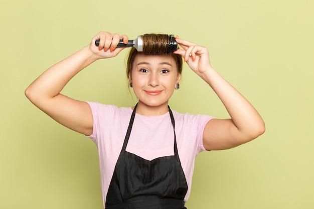 분홍색 티셔츠와 검은 망토의 전면보기 젊은 여성 미용사 헤어 브러시가 녹색에 미소와 함께 그녀의 머리를 고정