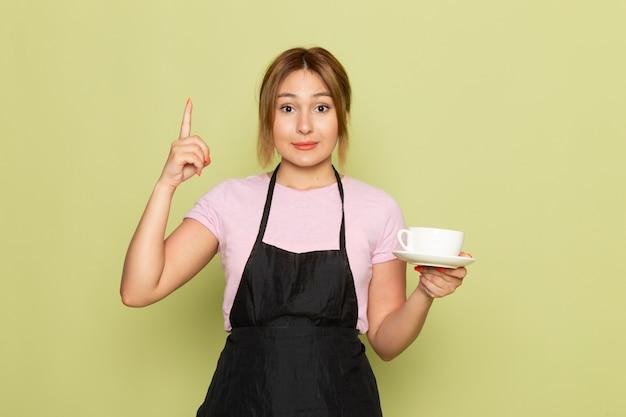 분홍색 티셔츠와 녹색에 웃는 컵을 들고 검은 케이프에 전면보기 젊은 여성 미용사