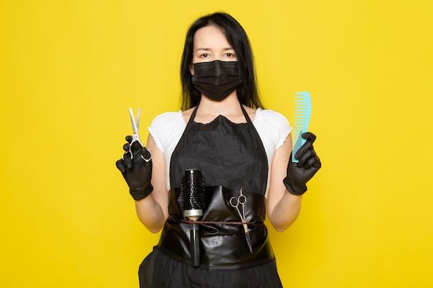 검은 살균 마스크 검은 장갑에 파란색 빗과 가위를 들고 흰색 티셔츠 검은 케이프의 전면보기 젊은 여성 미용사