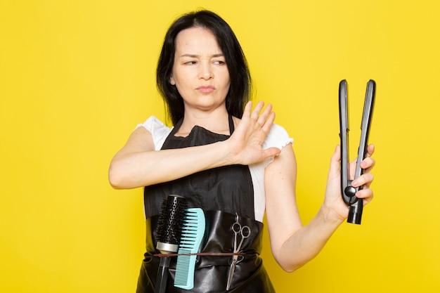 흰색 t- 셔츠 검은 망토 머리 도구 걱정 식을 들고 전면보기 젊은 여성 미용사