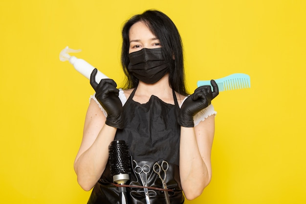검은 살균 마스크 검은 장갑에 스프레이와 빗을 들고 흰색 티셔츠 검은 케이프의 전면보기 젊은 여성 미용사