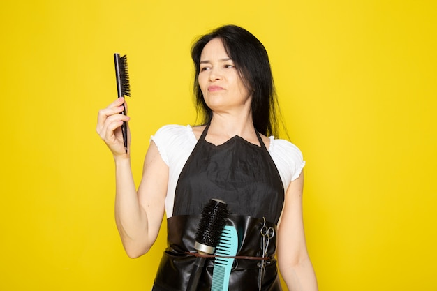 검은 브러시 웨이브 머리를 사용하여 흰색 티셔츠 검은 케이프의 전면보기 젊은 여성 미용사 불쾌