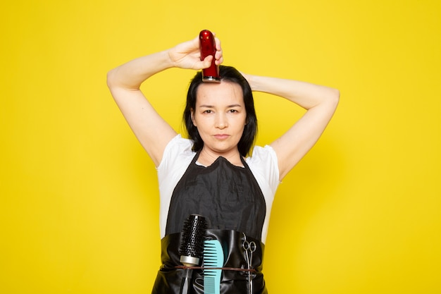 기계적인 머리 기계 파 머리를 사용 하여 흰색 티셔츠 검은 케이프에서 전면보기 젊은 여성 미용사