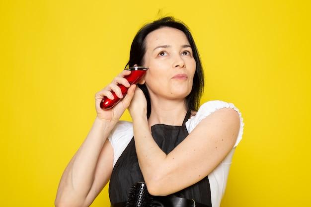 Вид спереди молодая женщина-парикмахер в белой футболке черная накидка с использованием механических волос машинная укладка волос