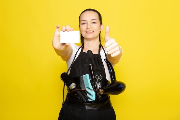 ブラシと白いカードのポーズを保持しているドライヤー付きの白いtシャツの黒いケープの正面の若い女性美容師