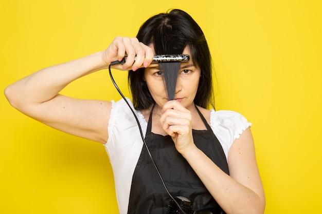 彼女の髪の波の髪を修正するブラシで白いtシャツの黒いケープの正面の若い女性美容師