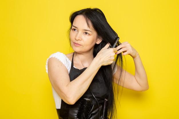 Вид спереди молодой женщины-парикмахера в белой футболке, черной накидке с кисточками для укладки волос