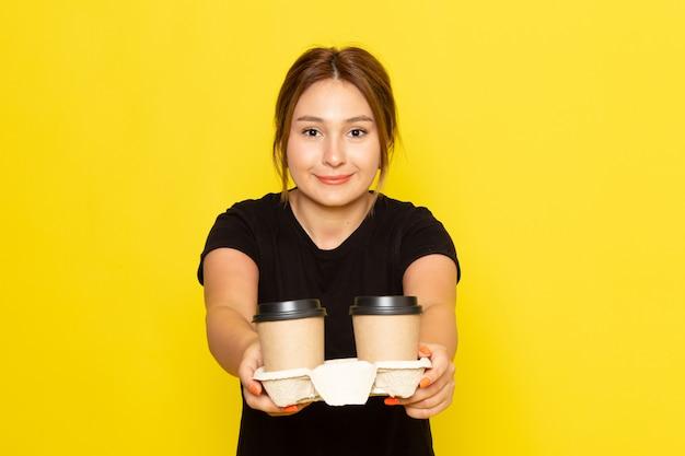 Вид спереди молодой женщины в черном платье, держащей кофейные чашки с улыбкой на лице на желтом
