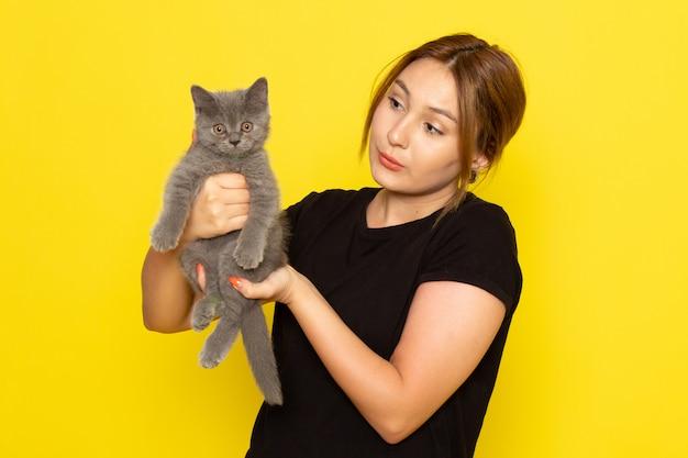 Вид спереди молодая женщина в черном платье держит милого котенка на желтом