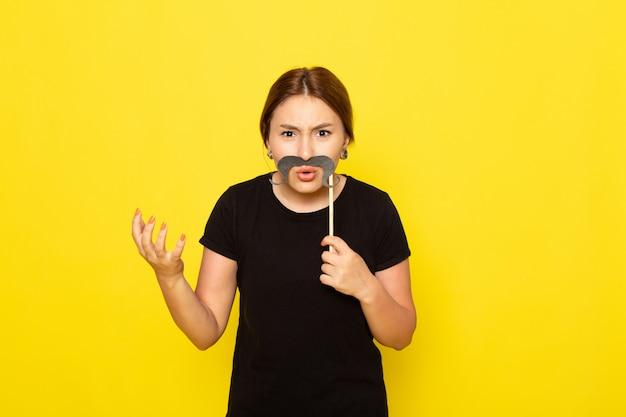 黄色の不機嫌な表情で偽の口ひげでポーズ黒のドレスで正面の若い女性