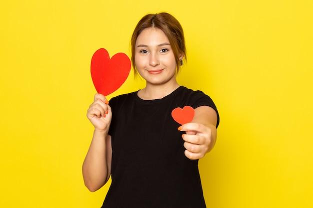 Молодая женщина в черном платье позирует с красными сердечками, улыбаясь на желтом