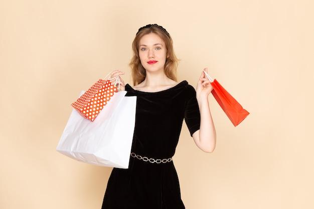 베이지 색에 패키지를 들고 체인 벨트와 검은 드레스에 전면보기 젊은 여성 무료 사진