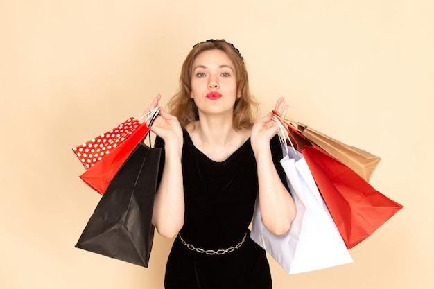 ベージュのショッピングパッケージを保持しているチェーンベルトと黒のドレスで正面の若い女性