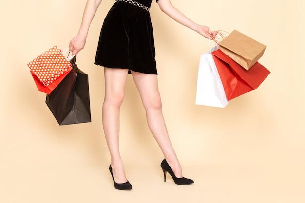 Вид спереди молодая женщина в черном платье с цепным поясом, держащая пакеты с покупками на бежевом
