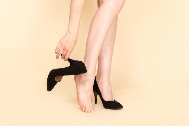 Вид спереди молодая женщина в черном платье с цепным поясом снимает туфли на бежевом