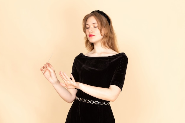 베이지 색에 그녀의 손톱을 사용하는 체인 벨트와 검은 드레스에 전면보기 젊은 여성