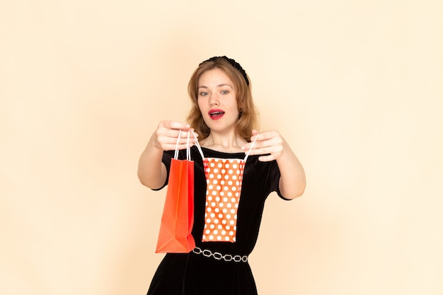 베이지 색에 패키지를 들고 체인 벨트와 검은 드레스에 전면보기 젊은 여성