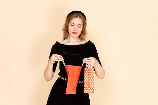 Вид спереди молодая женщина в черном платье с поясом с цепями, держащая пакеты на белом