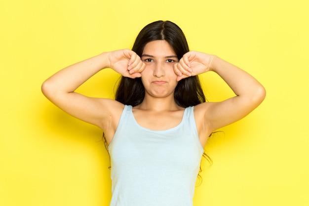 青いシャツのポーズと黄色の背景の女の子ポーズモデル美容若いで偽の泣きの正面の若い女性