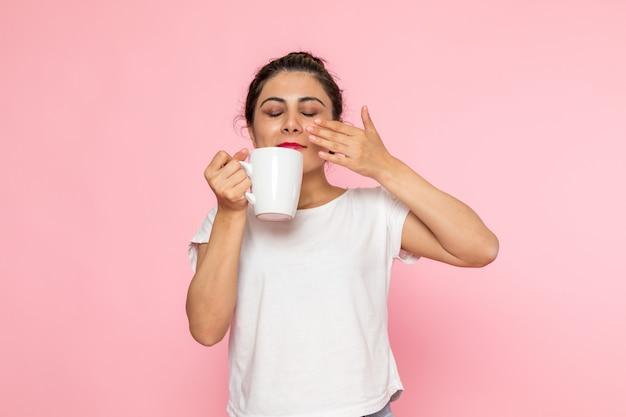 白いtシャツとブルージーンズのお茶を飲むの正面の若い女性