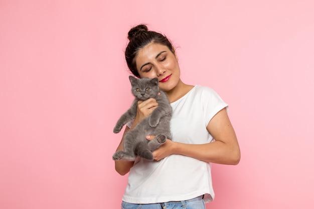 Вид спереди молодая самка в белой футболке и синих джинсах держит маленького милого серого котенка