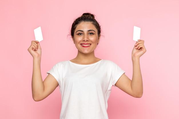 흰색 셔츠와 흰색 카드를 들고 청바지에 전면보기 젊은 여성
