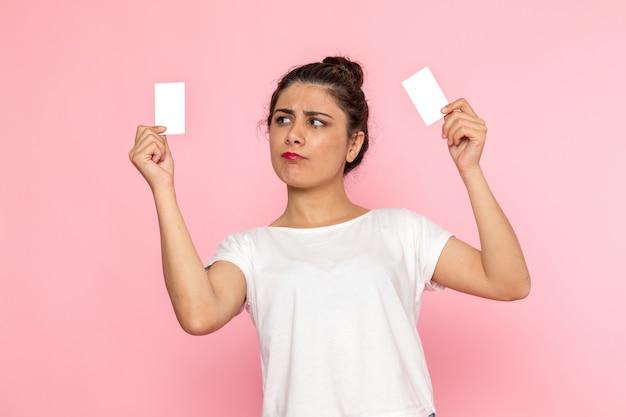 白いtシャツとブルージーンズの白いカードを保持している正面の若い女性